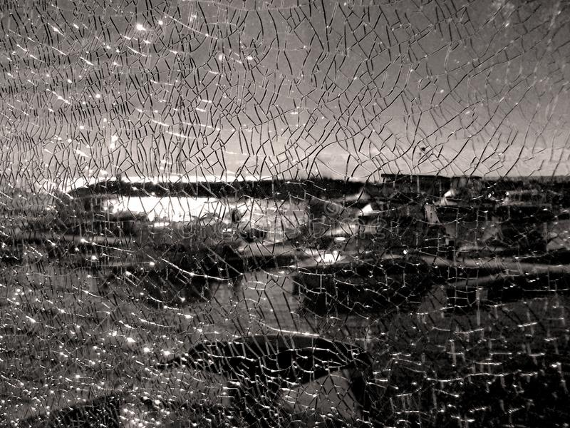 Through the shattered glass fencing visible pier, parking the boats. Texture cracked broken glass. royalty free stock photo