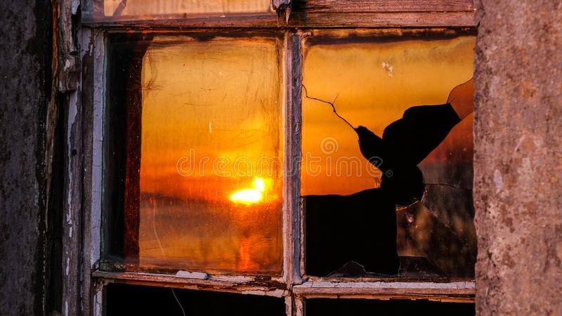 A shattered glass reflecting the sunset in Scotland. stock image