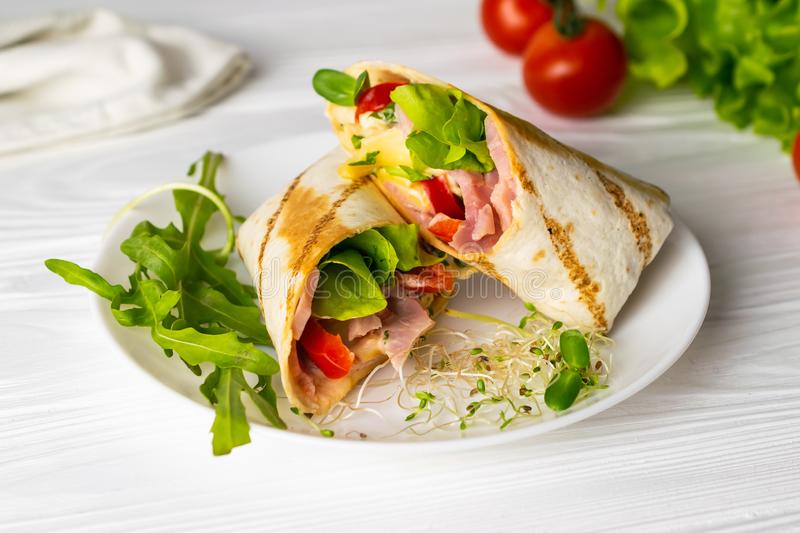 Shaurma wrapped sandwich with lettuce tomatoes ham and cheese stock photos