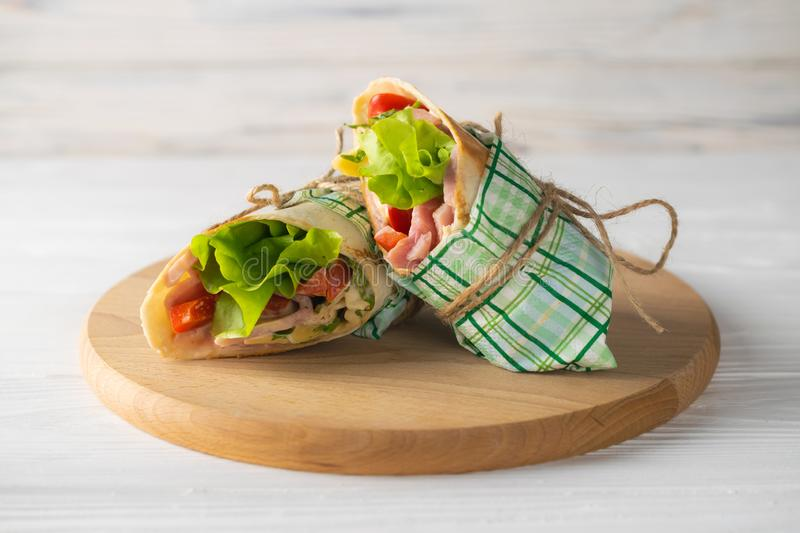 Shaurma wrapped sandwich with lettuce tomatoes ham and cheese royalty free stock image
