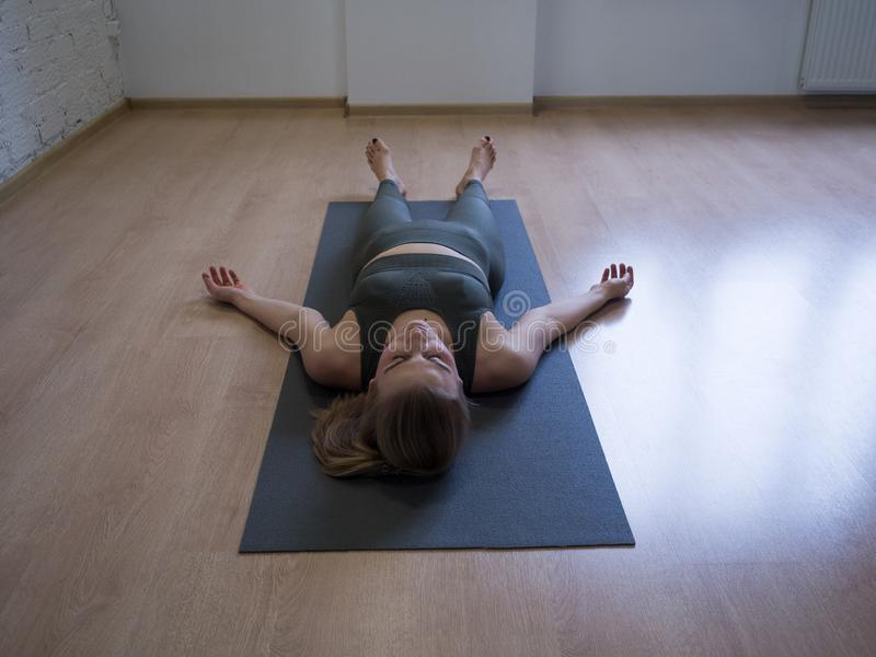 The shavasana. Woman laying on mat in relaxing pose on the floor, yoga class, front view royalty free stock image