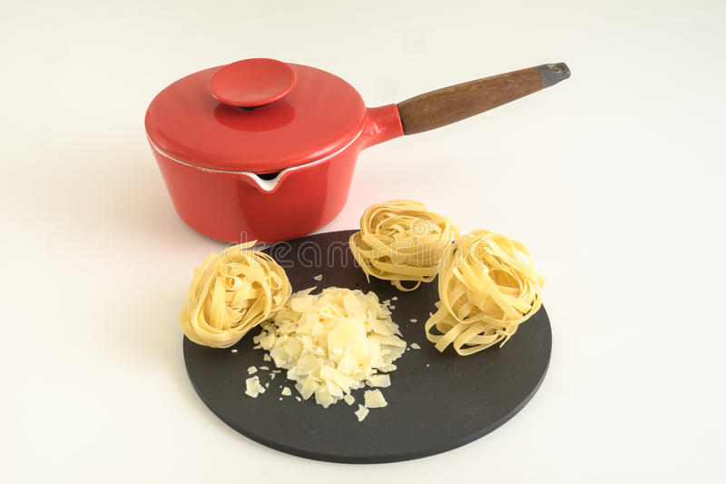 Shaved cheese and pasta with red pan. Shaved cheese and pasta ready for cooking stock photos