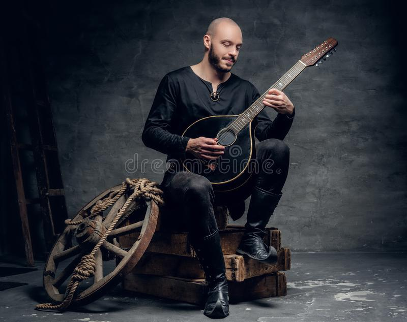 Traditional folk musician dressed in vintage Celtic clothes sits on a wooden box and plays mandolin. Shaved head traditional folk musician dressed in vintage royalty free stock photos