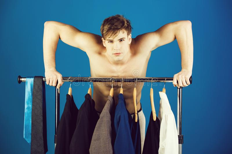 Shaved man with naked muscular torso standing at wardrobe hanger. With formal outfit of jacket, tie, shirt and suit on blue background stock photography