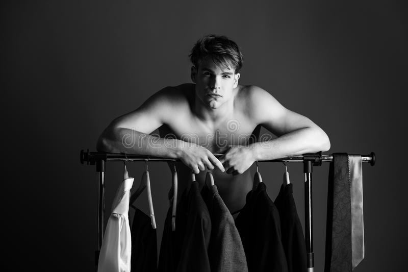 Shaved man with naked muscular torso standing at wardrobe hanger. Wardrobe. shaved man with naked muscular torso standing at wardrobe hanger with formal outfit stock images
