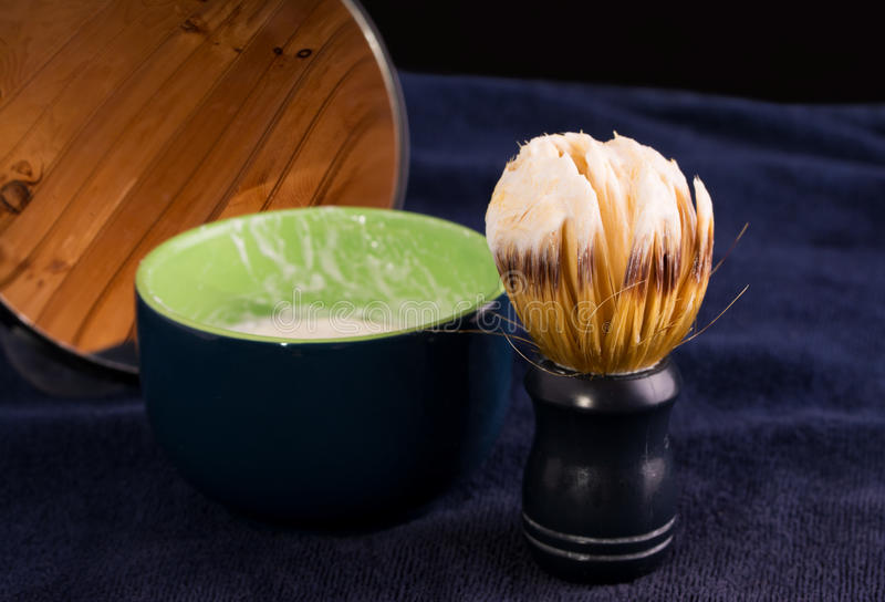 Shaving brush with foam, soap cup and mirror royalty free stock photo