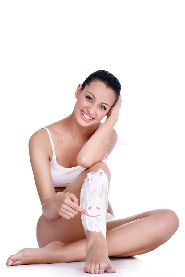 Shaving legs, smiley in shaving foam. Shaving legs, Young woman drawing smiley in shaving foam stock photos
