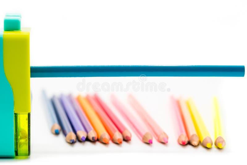 Shavings för vässare för pastellblåttguling roterande med träfärgrika blyertspennor som isoleras på vit bakgrund, tillbaka till s royaltyfri bild