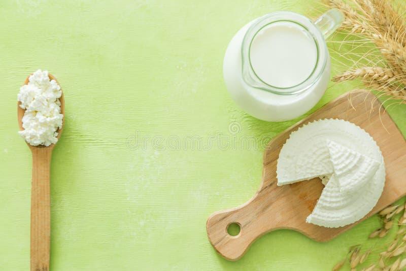 Shavuot-Konzept - Milchprodukte und Weizen auf grünem hölzernem Hintergrund stockfotos