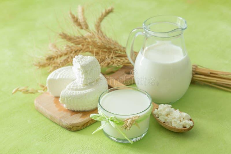 Shavuot-Konzept - Milchprodukte und Weizen auf grünem hölzernem Hintergrund lizenzfreie stockbilder