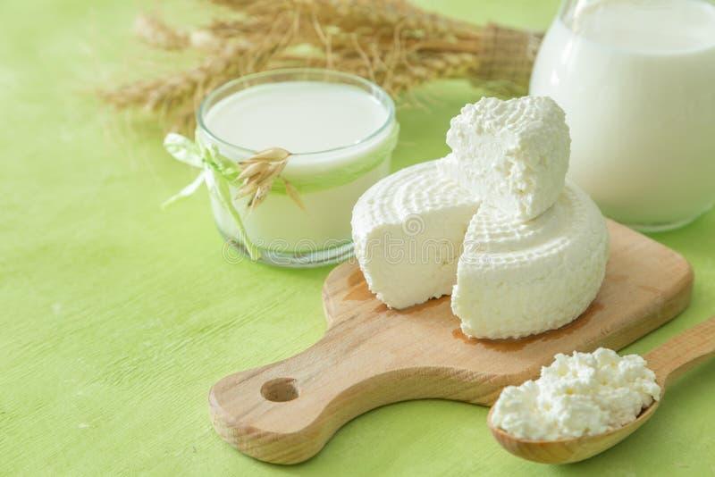Shavuot-Konzept - Milchprodukte und Weizen auf grünem hölzernem Hintergrund stockfoto