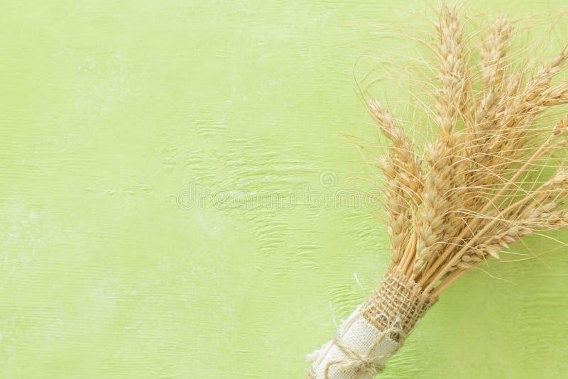 Shavuot-Konzept - Milchprodukte und Weizen auf gr?nem h?lzernem Hintergrund lizenzfreie stockbilder