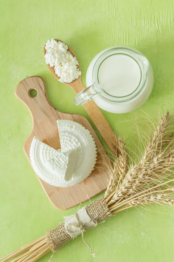 Shavuot-Konzept - Milchprodukte und Weizen auf gr?nem h?lzernem Hintergrund lizenzfreies stockbild