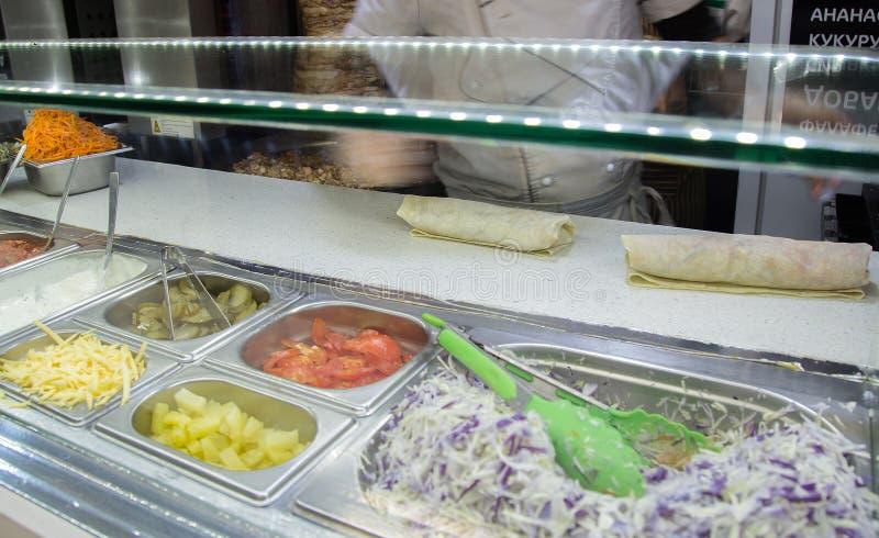 Shawarma在一皮塔饼的鸡卷与新鲜蔬菜和奶油 免版税库存照片