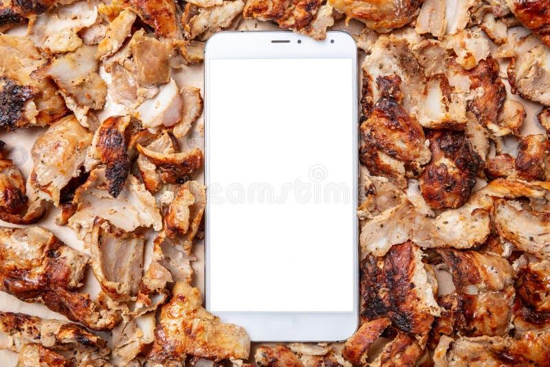 Shawarma,电罗经,网上命令 传统土耳其语,希腊肉食物和一个手机 免版税图库摄影