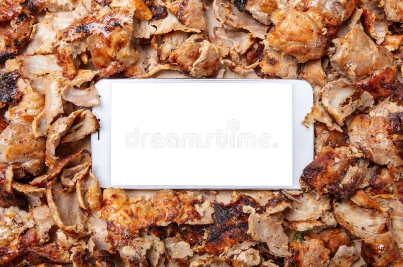 Shawarma,电罗经,网上命令 传统土耳其语,希腊肉食物和一个手机 库存照片