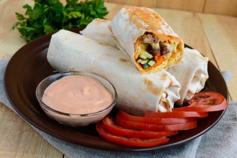 Shawarma -中东(阿拉伯)盘皮塔饼(lavash)充塞与:烤肉,调味汁,菜 图库摄影