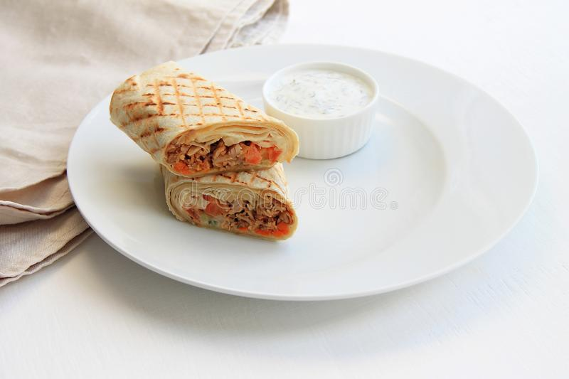 Shawarma with chicken, vegetables on a plate next to the sauce, light background. royalty free stock photo