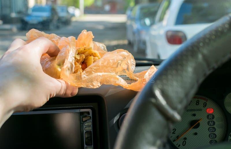 Shawarma dans la main du conducteur dans la voiture photographie stock libre de droits