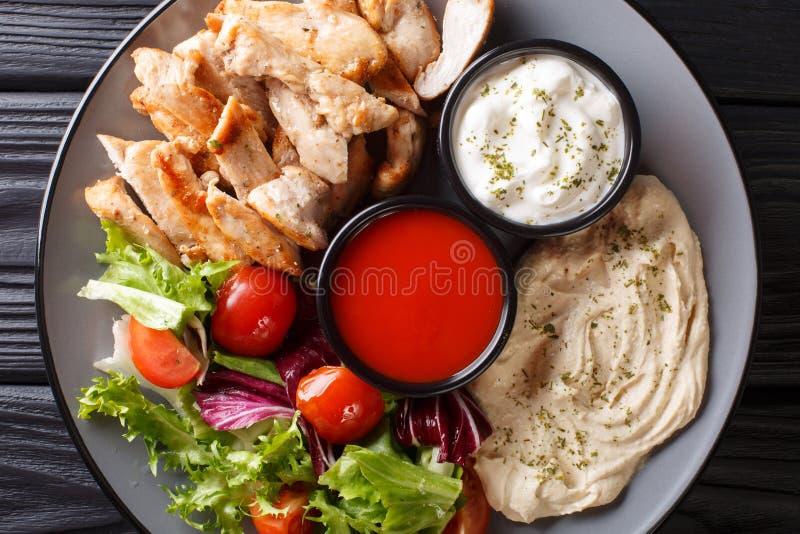 Shawarma de poulet avec le houmous, les légumes et la sauce servant sur un plan rapproché de plat vue supérieure horizontale image stock