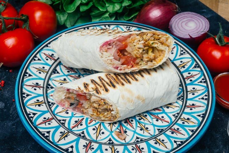 Shawarma do no espeto de Doner ou envoltório do doner Galinha grelhada no pão do pão árabe do lavash com legumes frescos - tomate foto de stock royalty free