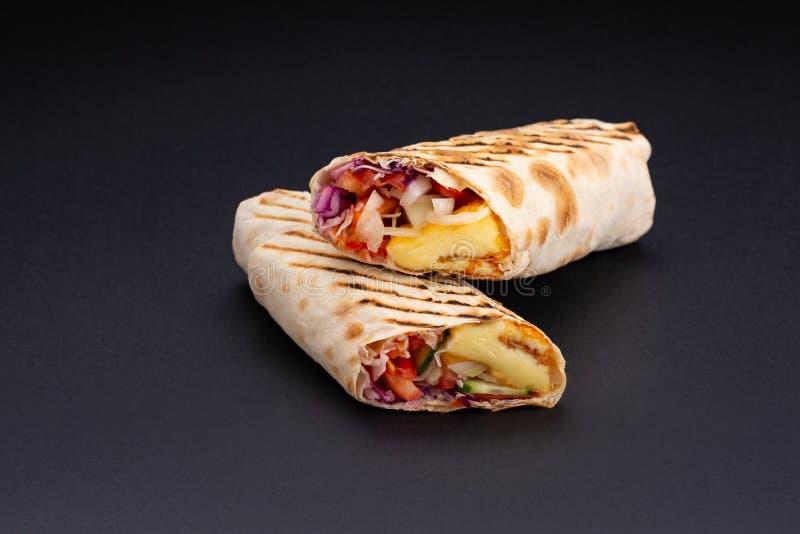 Shawarma en pain pita est coupé et se trouve sur un fond réfléchi noir Le plat du Moyen-Orient est préparé sur photographie stock