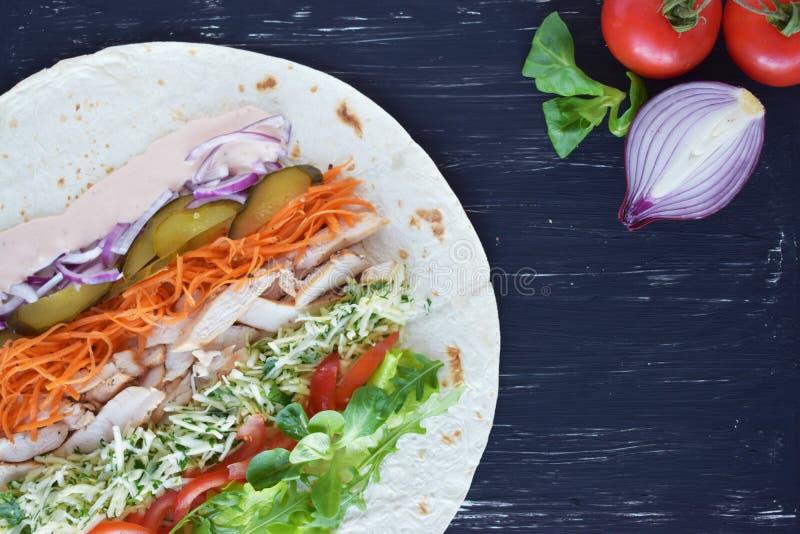 Shawarma fait maison avec le filet de viande de poulet et les légumes frais au-dessus du conseil noir en bois Cuisson des proces  photos stock