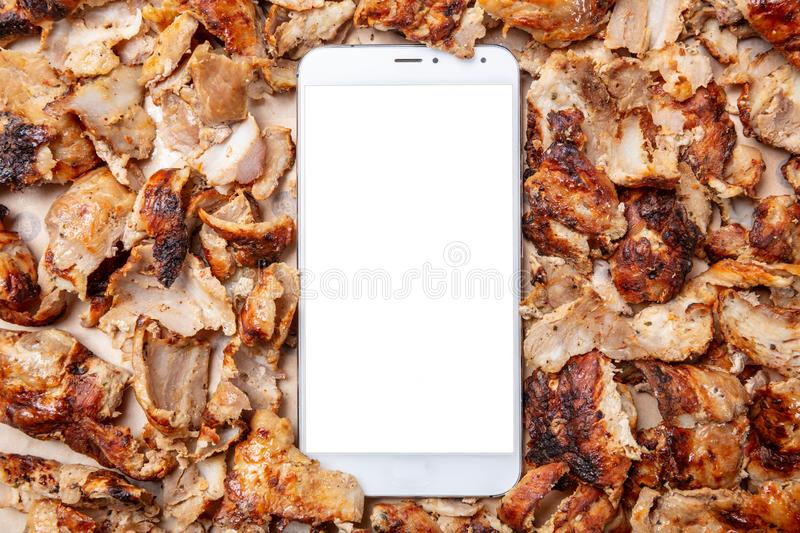Shawarma, gyros, online order. Traditional turkish, greek meat food and a mobile phone royalty free stock photography