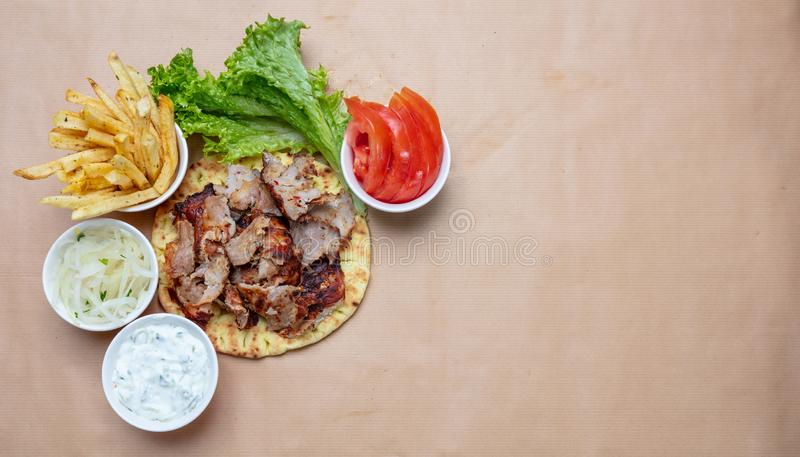 Shawarma, gyros on pita bread, vegetables and tzatziki sauce, top view. Traditional turkish, greek meat food stock image