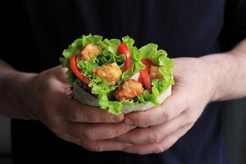 Shawarma in male hands. Doner kebab. Shawarma with meat, onions, salad and tomato. Eastern food stock image