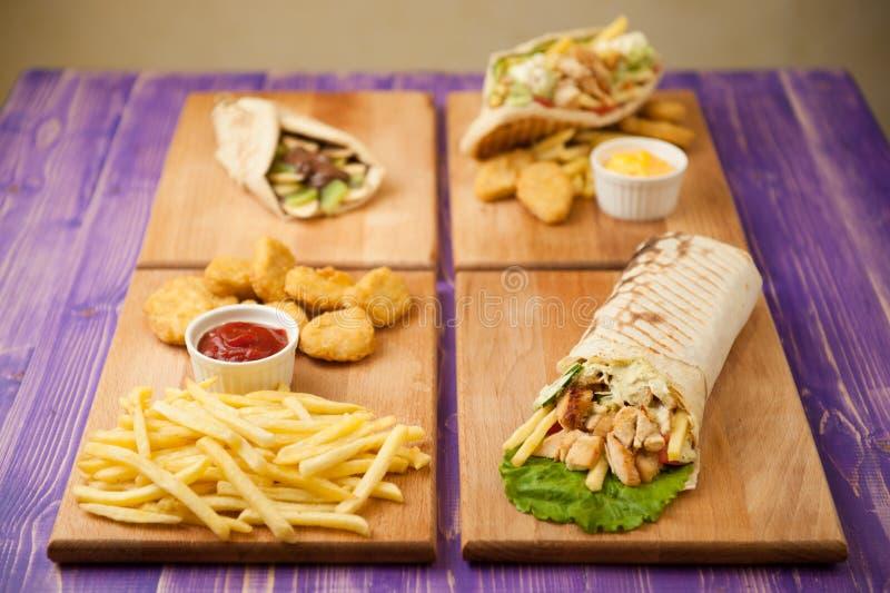 Shawarma, pepite e patate fritte, girobussola greca e pita con cioccolato ed il kiwi su una tavola immagini stock