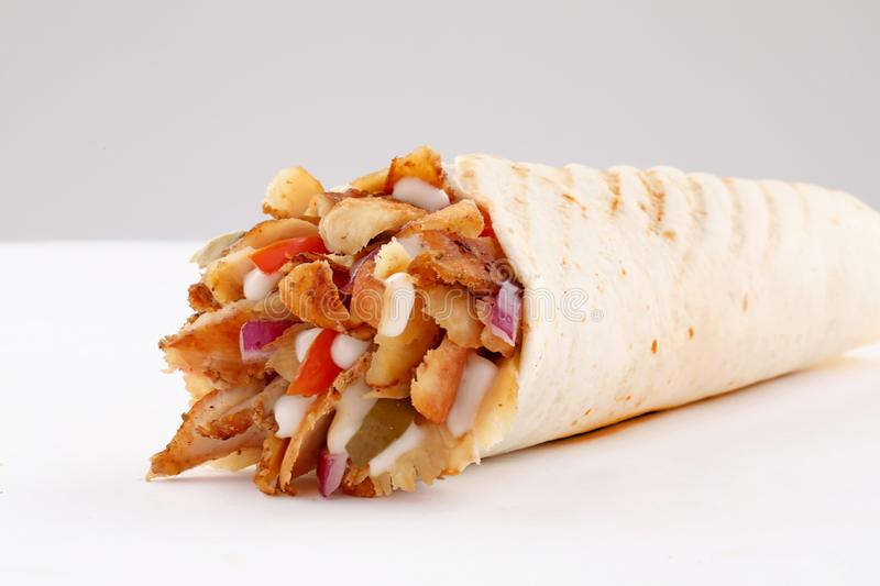 Shawarma wrap with onion and sauce on white background. Shawerma, shawarma tourtilla wrap with onion, tomato, lettuce and garilc sauce on white background royalty free stock image