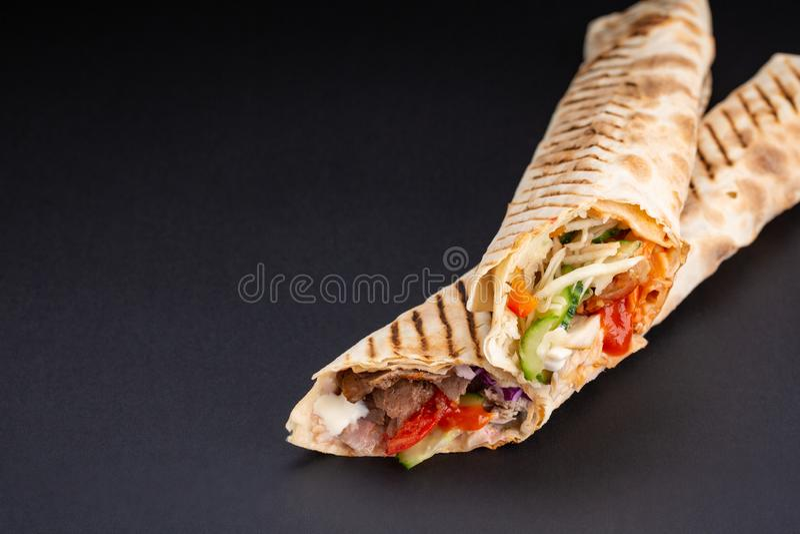 Shawarmasandwich - vers broodje van dun die lavash of pitabroodje met geroosterd vlees, paddestoelen, kaas, kool, wortelen, saus  stock afbeelding