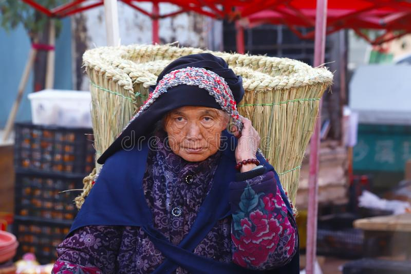An elderly woman carrying a big basket at the Shaxi market in Yunnan, China stock photos