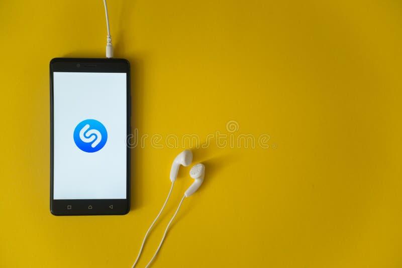 Shazamembleem op het smartphonescherm op gele achtergrond royalty-vrije stock afbeeldingen