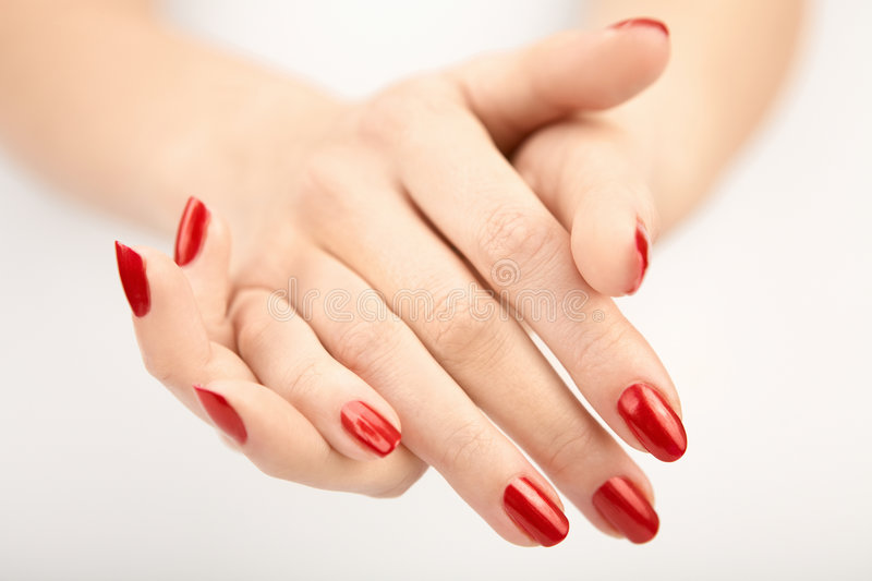 The sheaf. Sheaf of two well-groomed hands with the red manicure, isolated stock images