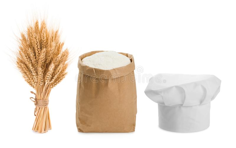 Sheaf of wheat, chefs hat and flour isolated on white royalty free stock photos