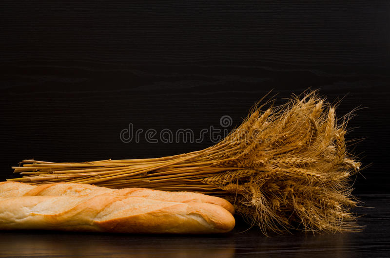 Sheaf and white loaves on a black background stock photos