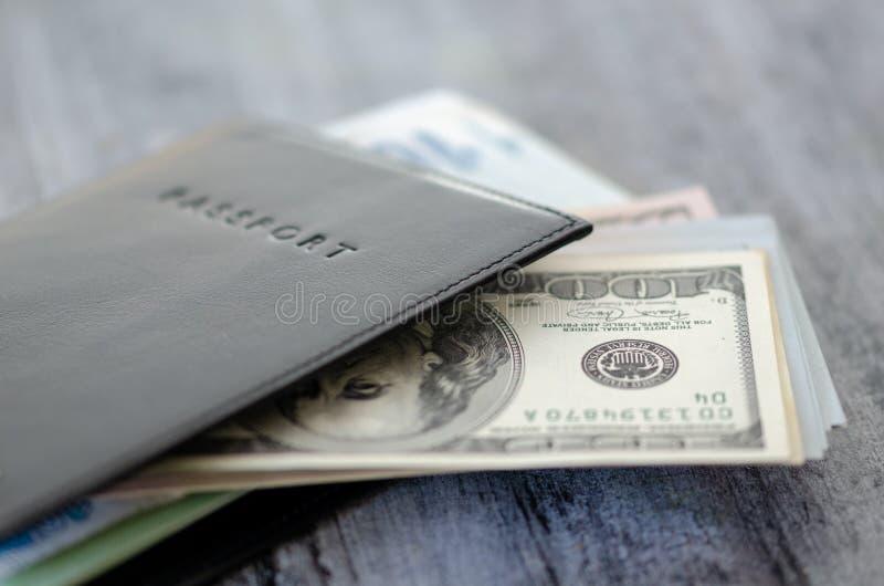 Sheathed paszporta i gotówki dolarów banknoty na tabl obraz stock