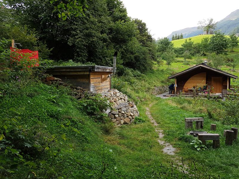 Cabin on the mountaintop. Shed next to a lodge on a hill with a path and a shower royalty free stock image