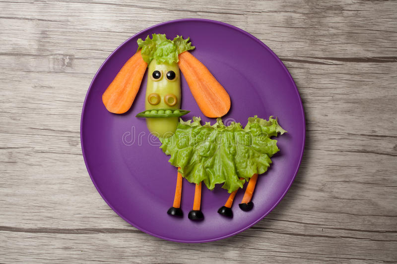 Sheep made of food on plate and table. Sheep made of salad, carrot, pepper, olive and pea. Shot with Canon 5D, ISO 100, on plate and wooden background.n stock photography