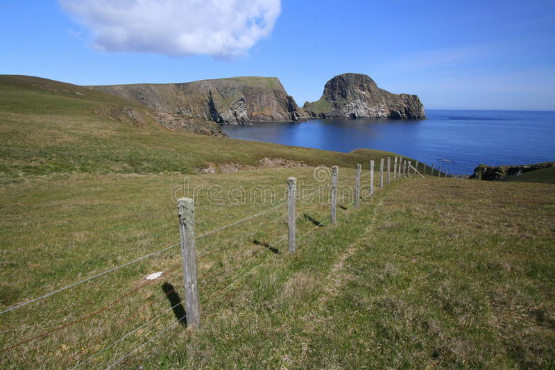 Fence and Sheep Rock. Field fence and Sheep Rock on Fair Isle in the Shetland Isles, Scotland royalty free stock image