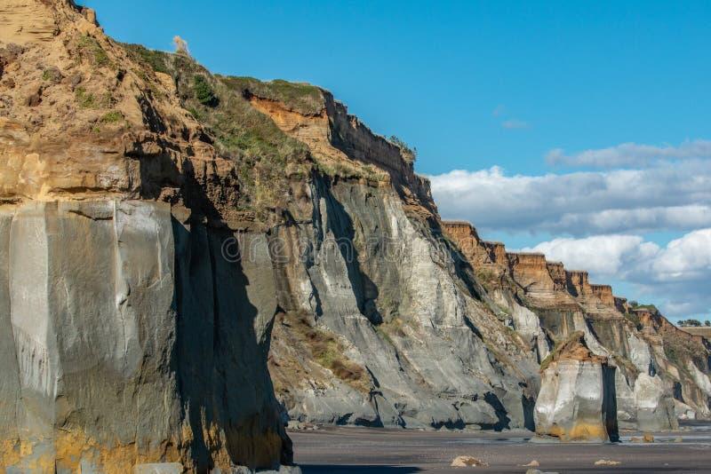 Sheer cliffs facing onto beach at Kai Iwi Beach in Whanganui stock images