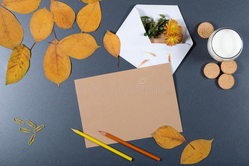 Sheet of brown craft paper, white envelope with hote and flower, yellow and orange leaves, color pencils, glass of milk and stock photography