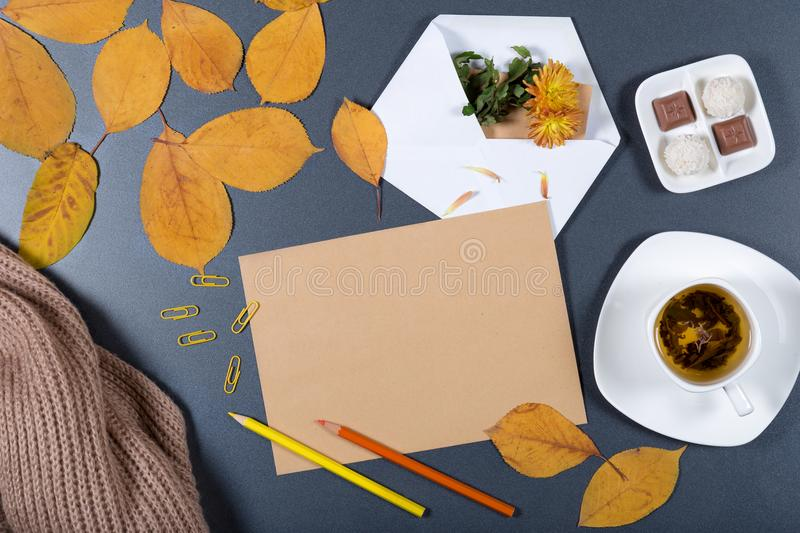 Sheet of brown craft paper, white envelope with note and flower, yellow and orange leaves, color pencils, cup of herbal tea and c stock photos
