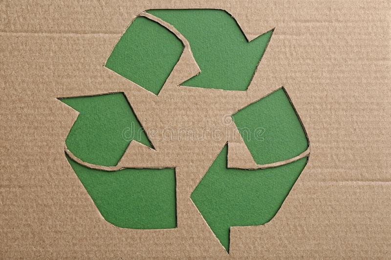 Sheet of cardboard with cutout recycling symbol on green background. Top view royalty free stock photography