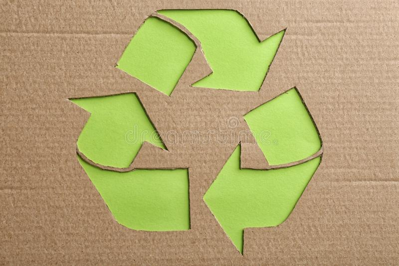 Sheet of cardboard with cutout recycling symbol on green background. Top view royalty free stock image