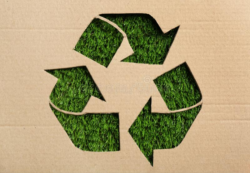 Sheet of cardboard with cutout recycling symbol. On green grass, top view stock photo