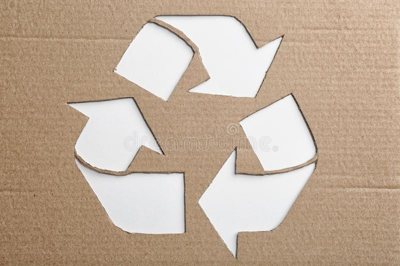 Sheet of cardboard with cutout recycling symbol on white background. Top view royalty free stock photos