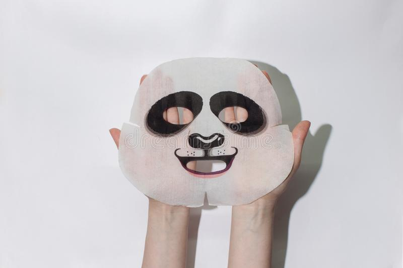 Sheet face mask. Fabric mask for facial skin. Female hands hold a face mask. stock photo